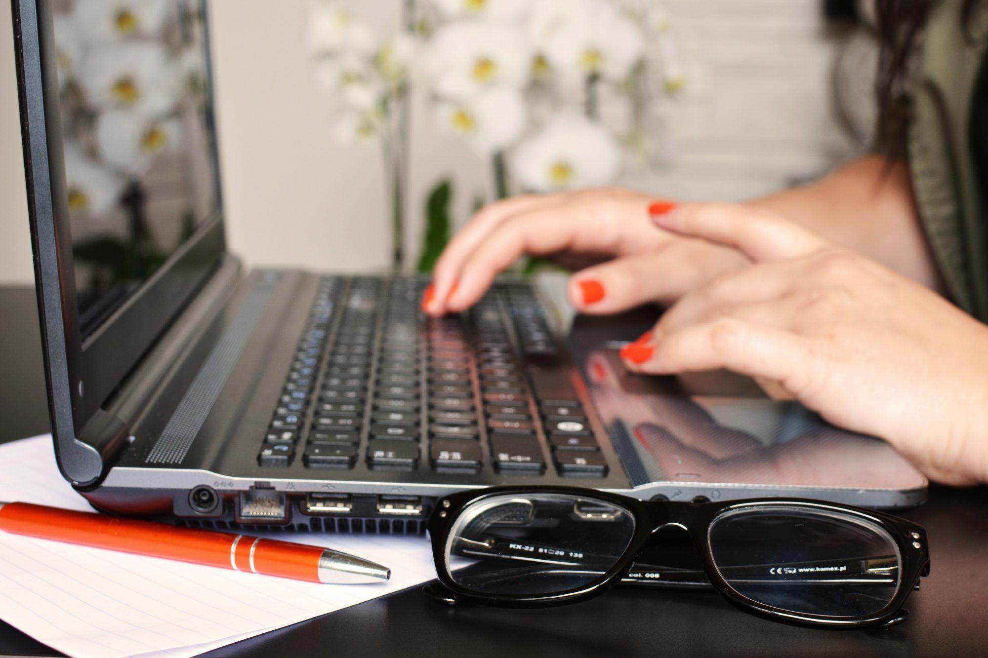 Žena za laptopom s okuliarmi položenými na stole